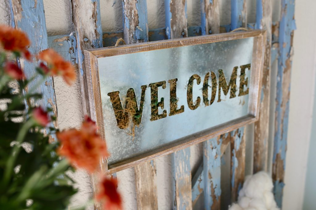 welcome sign layered on vintage gate for fall
