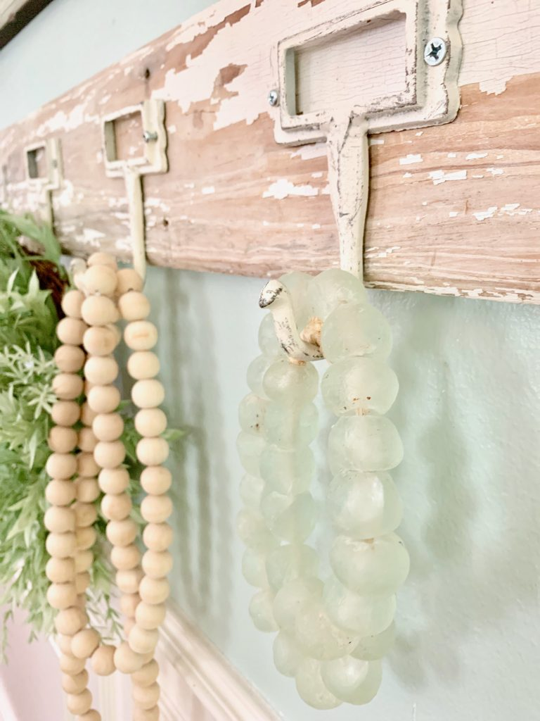 Hang decor beads on decorative wall hooks.