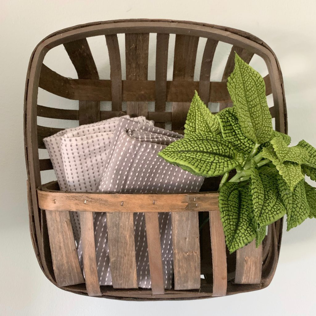 Folded tea towels and faux stems in tobacco wall basket.