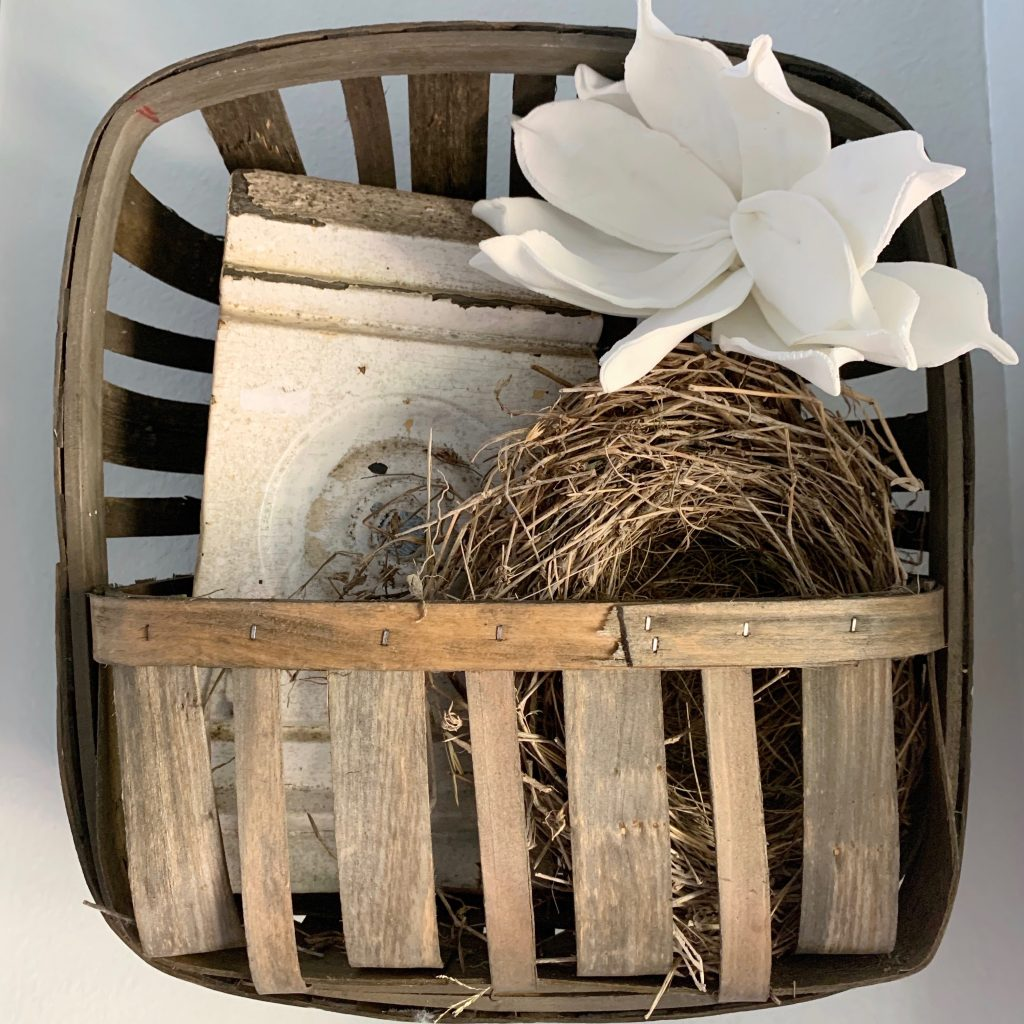 Tobacco wall basket filled with architectural salvage, birds nest and white magnolia blooms.