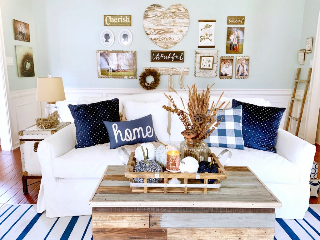 Cottage style living room decorated for Fall in warm wood tones and navy colors.